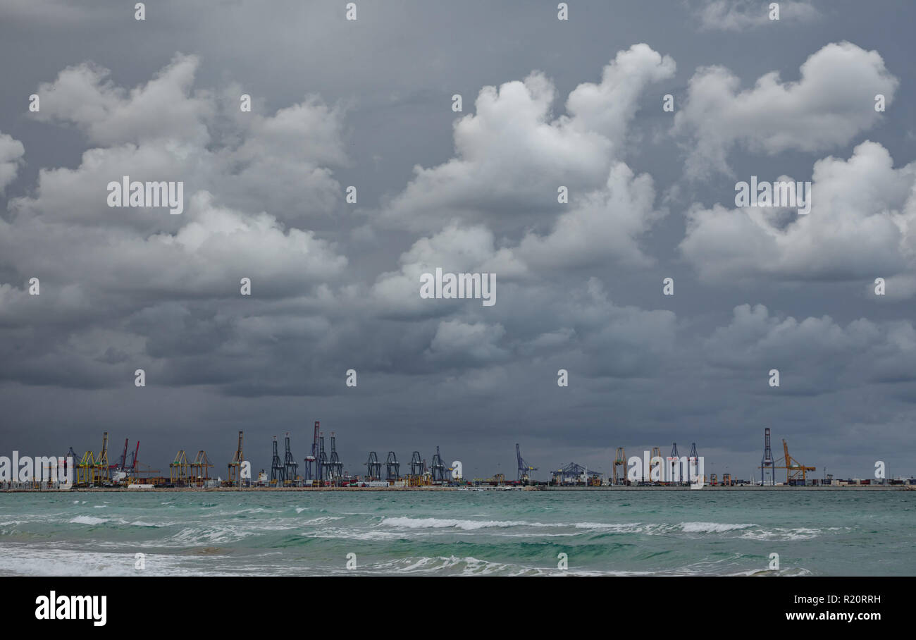 Very dark stormy clouds over commercial dock - Stock Image