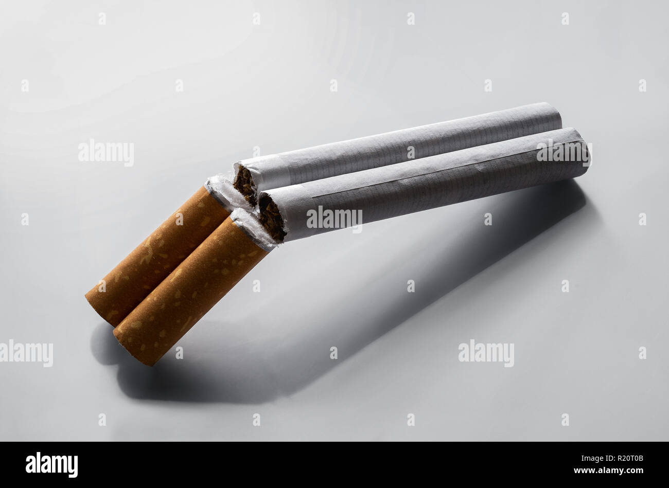 Quit smoking concept, two cigarettes as a double barrel rifle over gray background with copy space - Stock Image