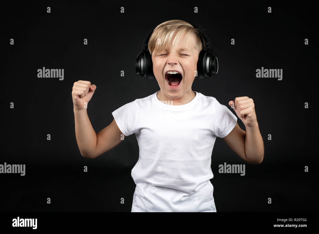 Little blond boy screams loudly with a headphone - Stock Image
