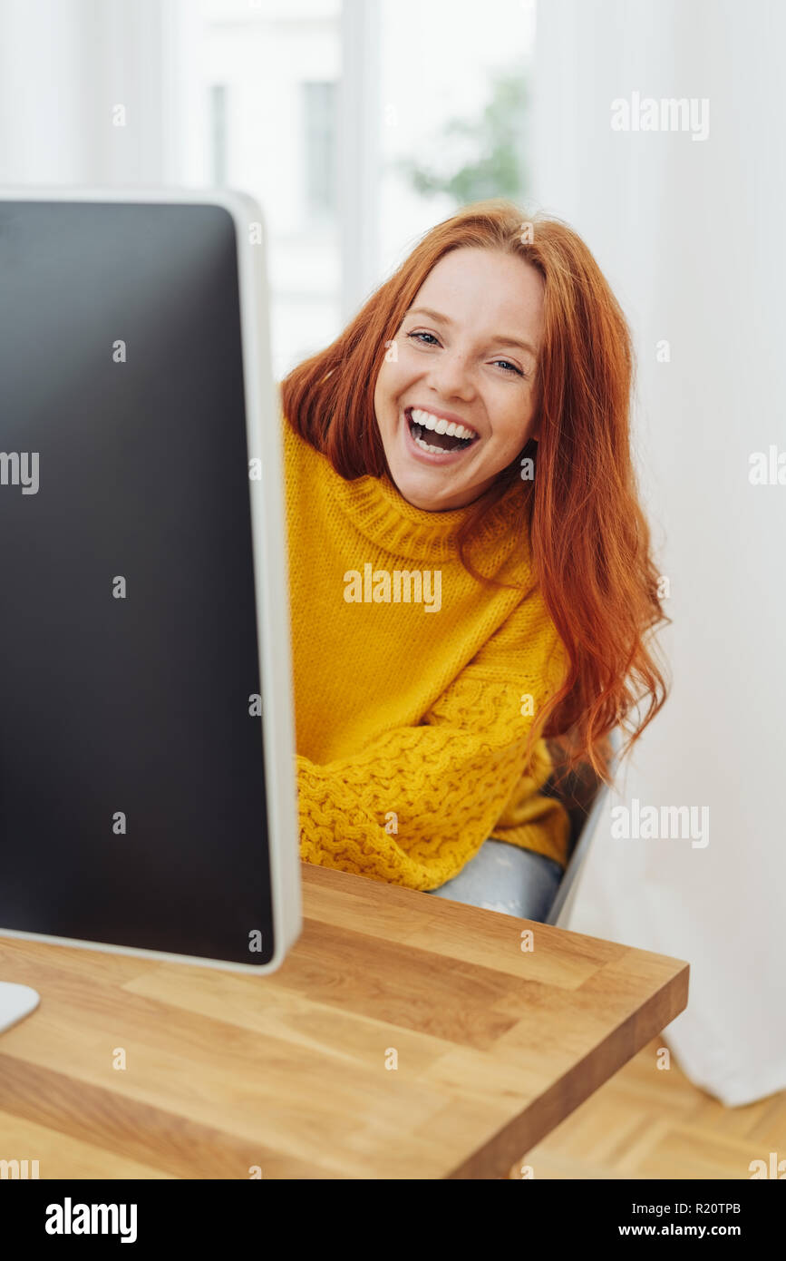 Young woman laughing merrily looking around the edge of her desktop monitor with a vivacious smile - Stock Image