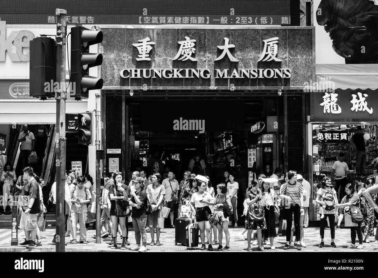 Hong Kong, China - May 16 2018:  People waiting to cross the street in front of the famous Chungking Mansions in Tsim Sha Tsui, Kowloon in Hong Kong. - Stock Image