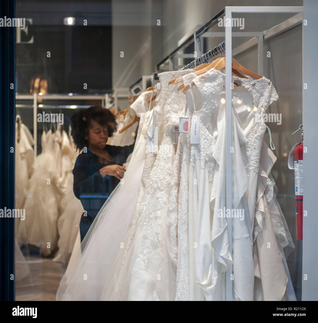 An employee arranges dresses in a David's Bridal store in the Chelsea neighborhood of New York on Sunday, November 11, 2018. David's Bridal is reported to be preparing a Chapter 11 bankruptcy filing if it cannot reach a deal with its creditors. The company has until November 14 to make the interest payment on its approximately $760 million in debt.  (© Richard B. Levine) - Stock Image