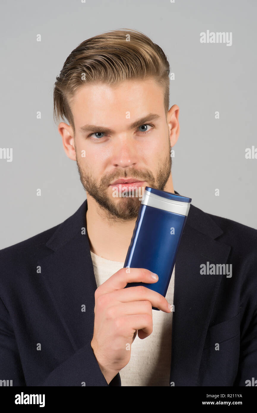Businessman with shampoo bottle. Bearded man hold gel tube. Hair care and skincare. Morning grooming at hairdresser salon or barbershop. Health and healthcare. Bodycare cosmetic for bath or shower. - Stock Image