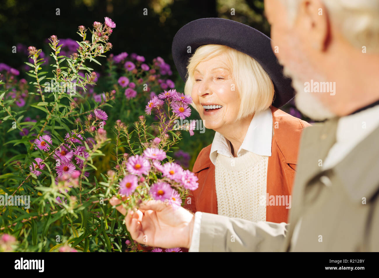 Positive happy aged woman enjoying flowers smell - Stock Image