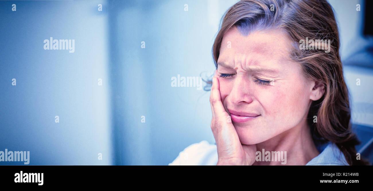 Unhappy woman having a toothache - Stock Image