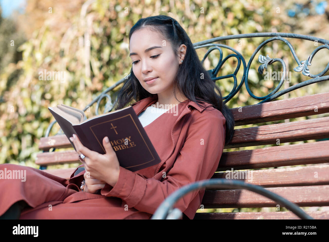 Relaxed Asian girl reading Holy Bible on air - Stock Image