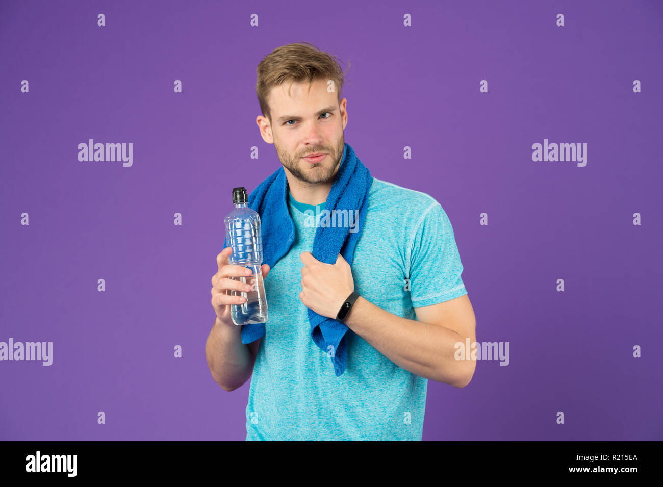 Stay hydrated. Drink some water. Man athlete with towel on shoulders holds water bottle. Man athlete sport clothes refreshing. Sport and healthy lifestyle concept. Athlete drink water after training. - Stock Image