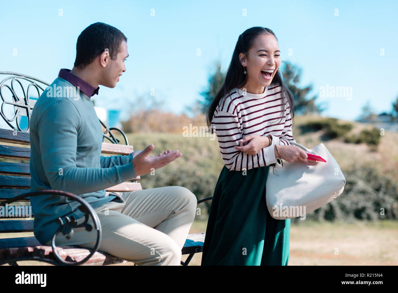 Joyful Asian female person laughing at her partner - Stock Image