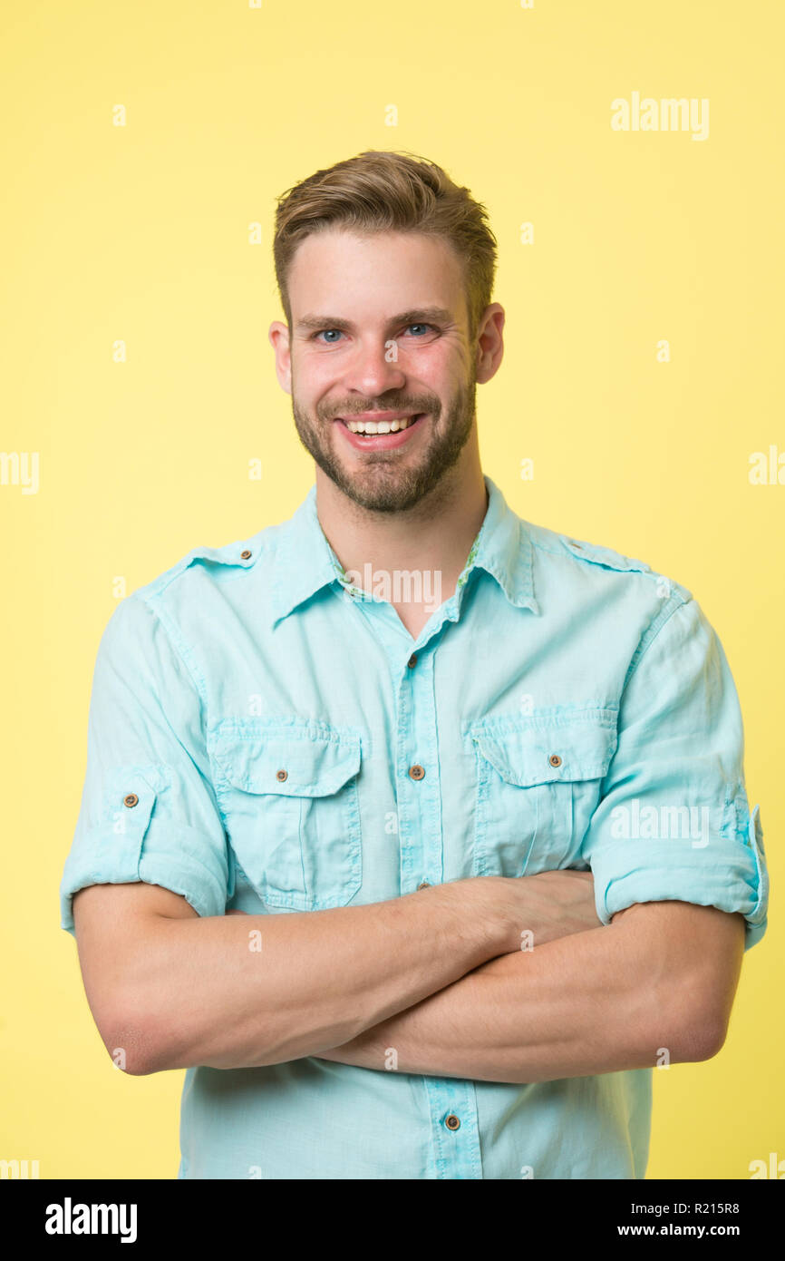 Cheerful consultant. Man smiling face posing confidently with folded arms yellow background. Man shop consultant looks cheerful confident and hospitable. Guy with bristle glad to help you in shop. - Stock Image