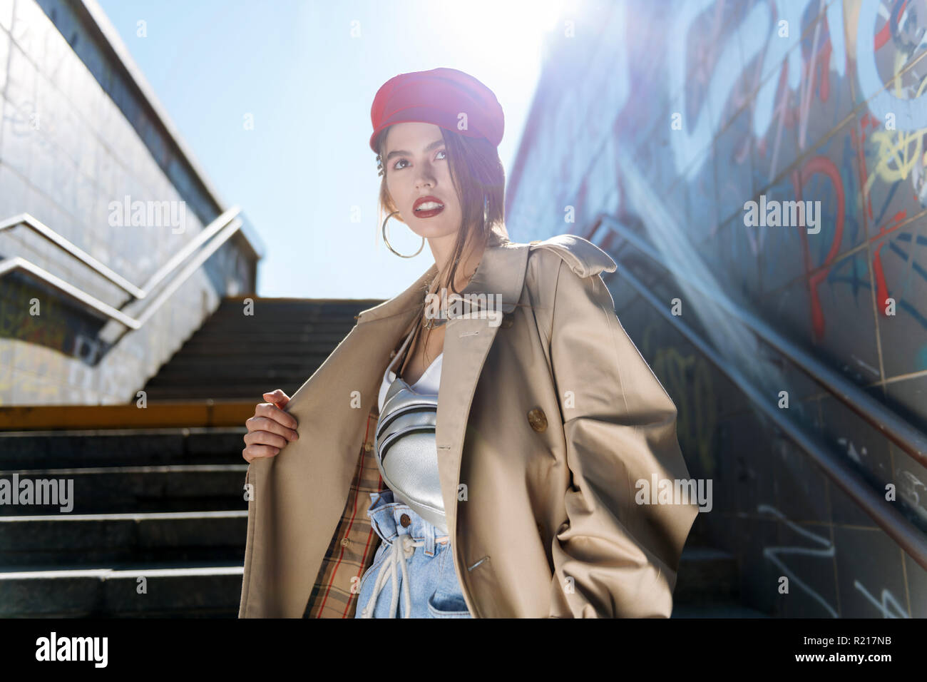Trendy model wearing beige trench coat and red beret posing - Stock Image