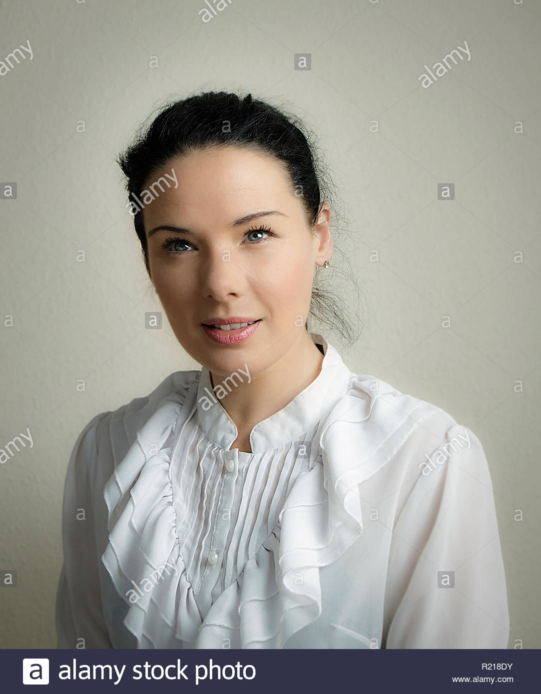 Head, shoulders and chest portrait of a dark haired woman wearing a frilly blouse, with blue eyes glinting in the subdued light. - Stock Image