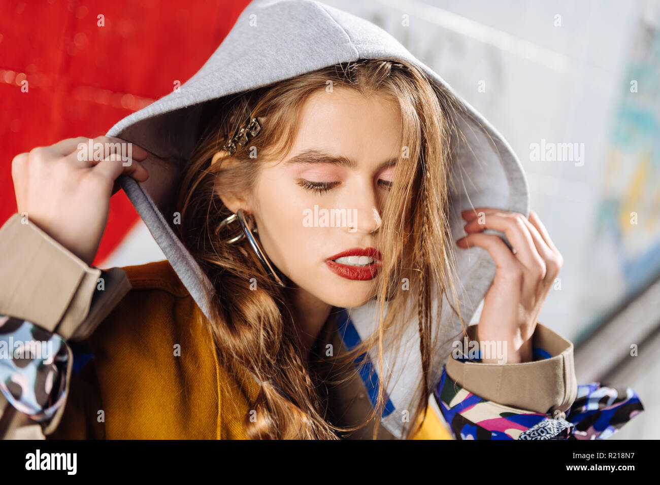 Portrait of beautiful photo model wearing trench coat with hoodie - Stock Image