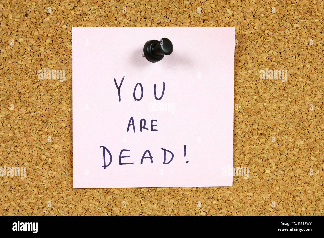 Pink sticky note pinned to an office notice board. You are dead - death threat, punishable crime. - Stock Image