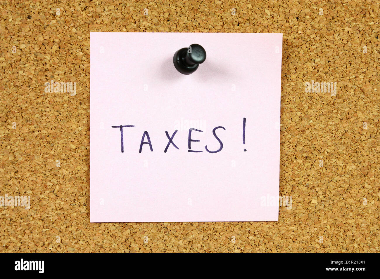 Pink sticky note pinned to an office notice board. Taxes reminder - you need to fill your income statement! - Stock Image