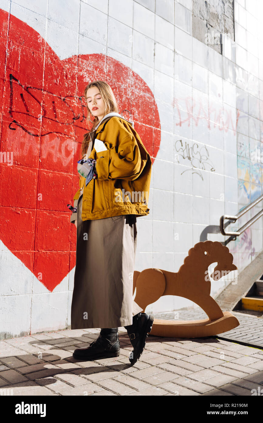 Fashion blogger wearing trendy bright oversize clothes posing for photo - Stock Image