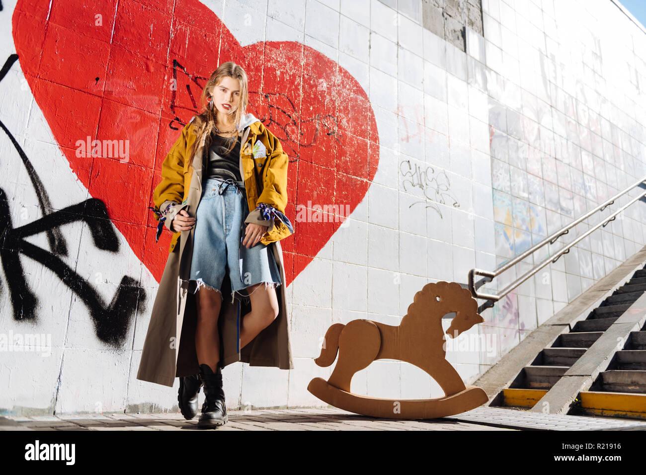 Stylish model wearing baggy denim shorts and oversize coat - Stock Image