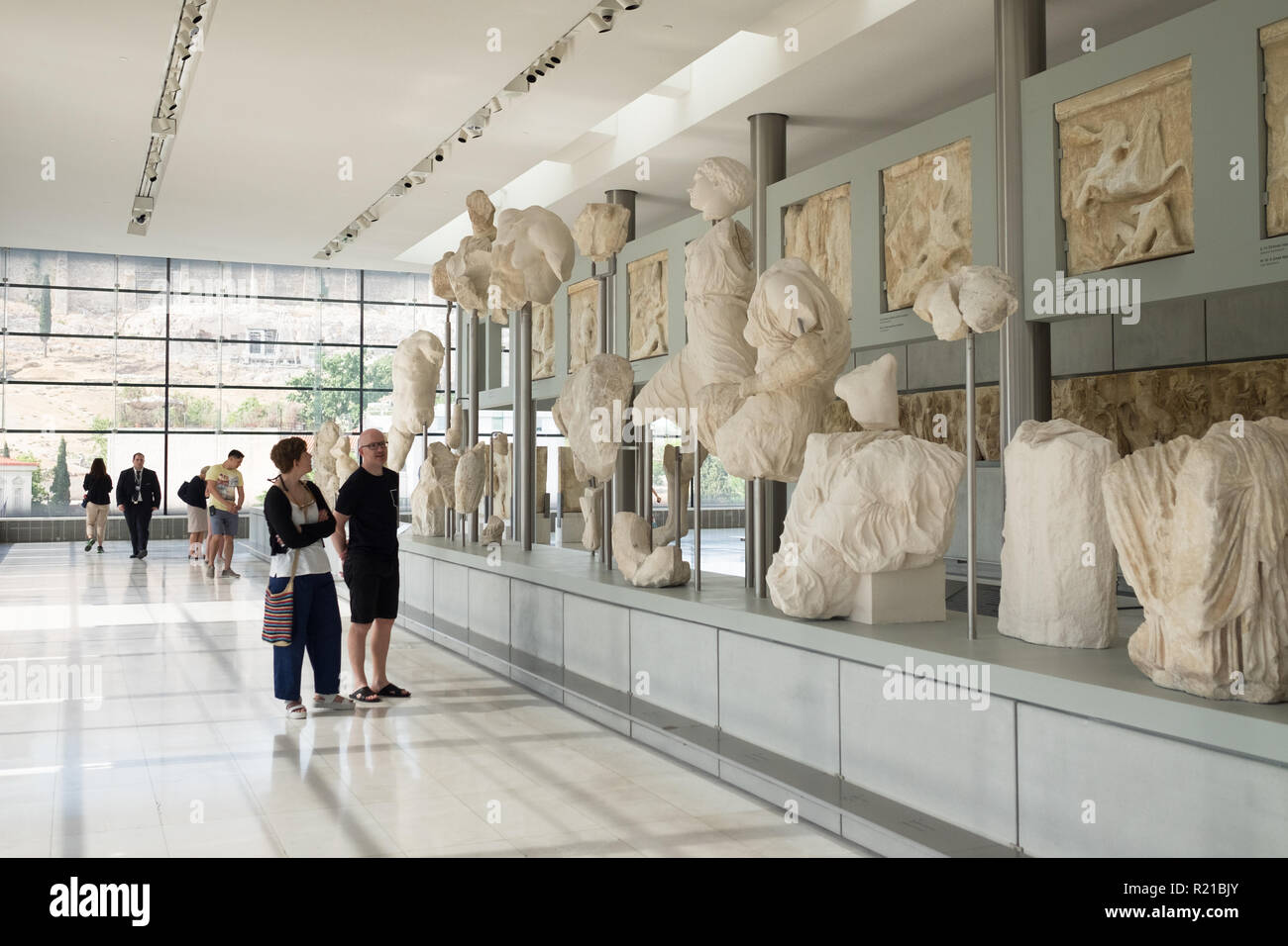 Tourists view the west pediment of the Parthenon in the Acropolis Museum in Athens, Greece - Stock Image