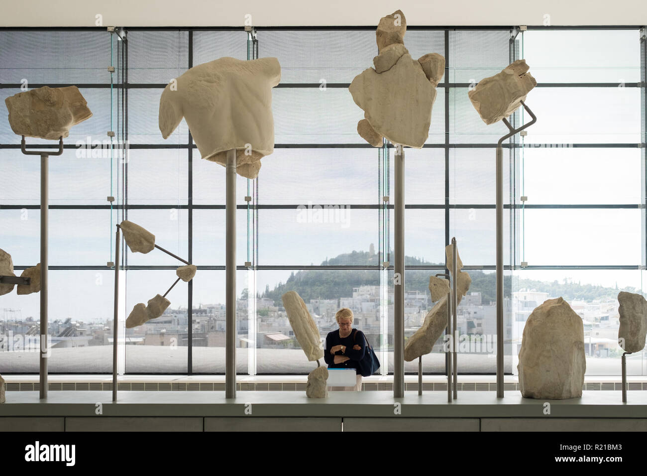 A tourist views the west pediment of the Parthenon in the Acropolis Museum in Athens, Greece Stock Photo