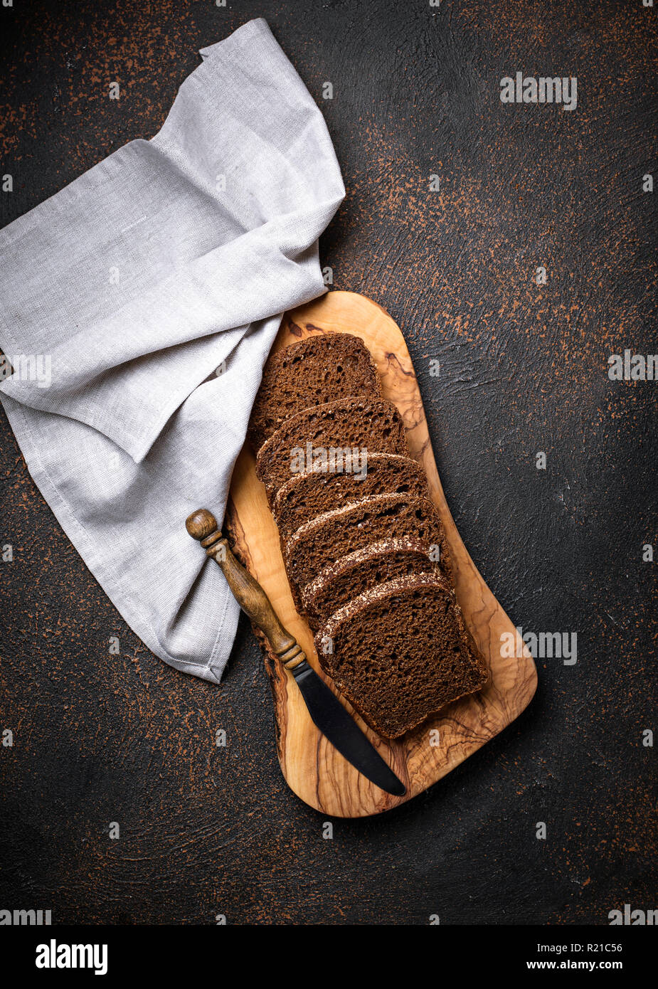 Fresh sliced rye bread on rusty background - Stock Image
