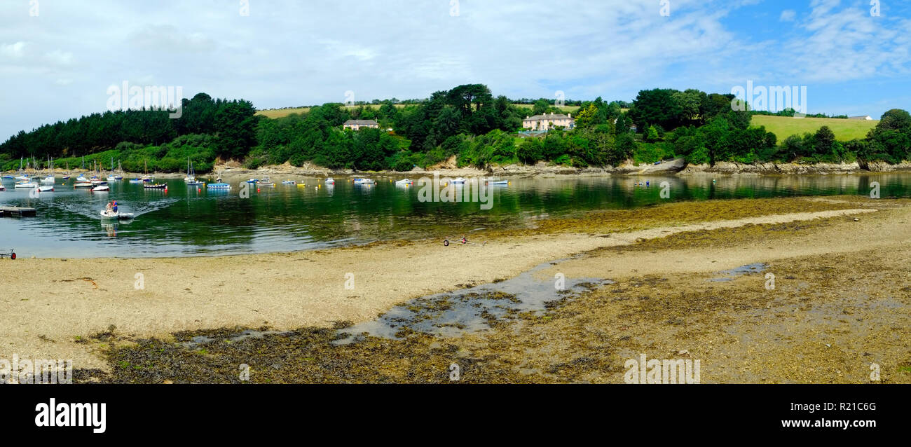 St Just in Roseland, UK - 25th July 2017: Low tide and a calm summer morning bring a few boats out onto the creek at St Just in Roseland on the picturesque Roseland Peninsula in Cornwall, UK Stock Photo