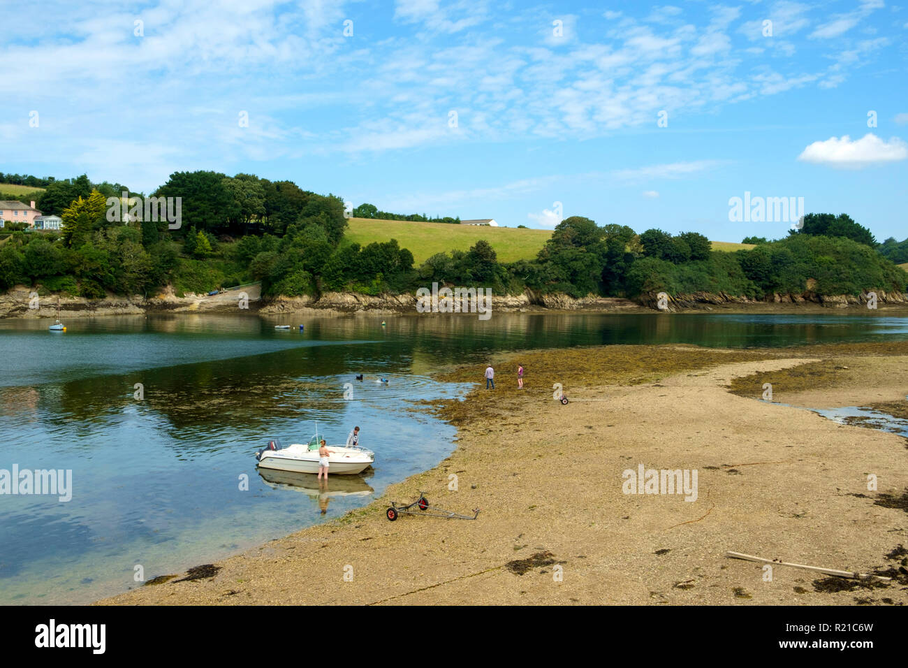 St Just in Roseland, UK - 25th July 2017: A calm summer morning brings people out to exercise their dogs by the creek at St Just in Roseland on the picturesque Roseland Peninsula in Cornwall, UK Stock Photo
