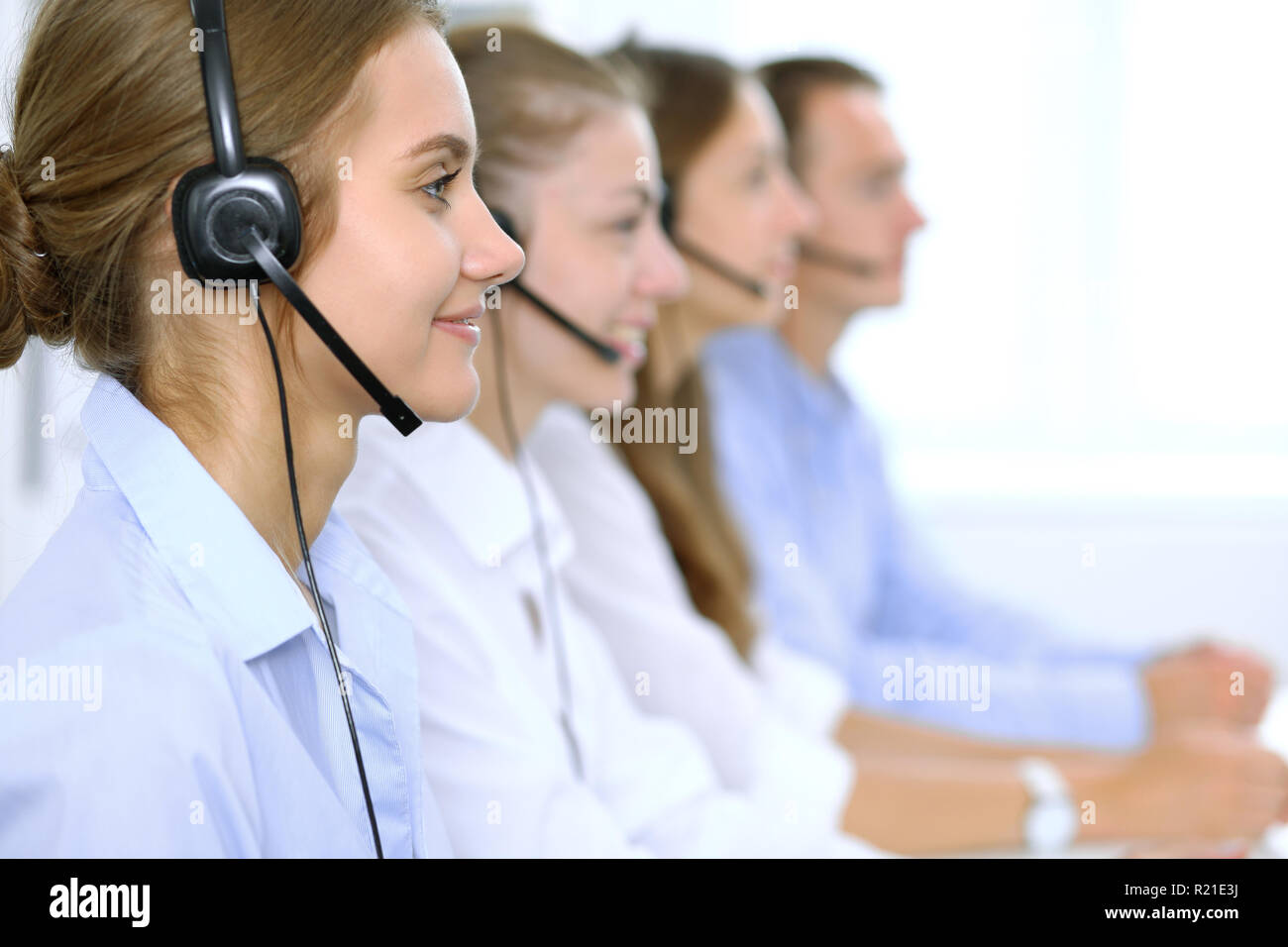 Call center operator in headset while consulting client. Telemarketing or phone sales Stock Photo