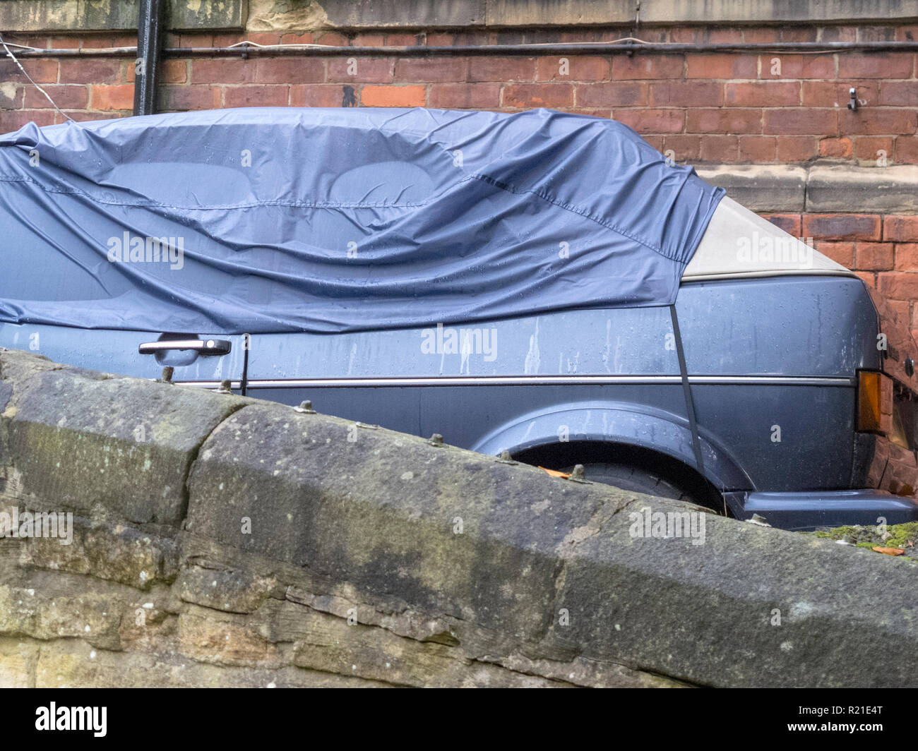 A blue VW Golf MK2 convertible hatchback car with a cover over it, parked next an old run down house in Durham City, County Durham, England, UK - Stock Image