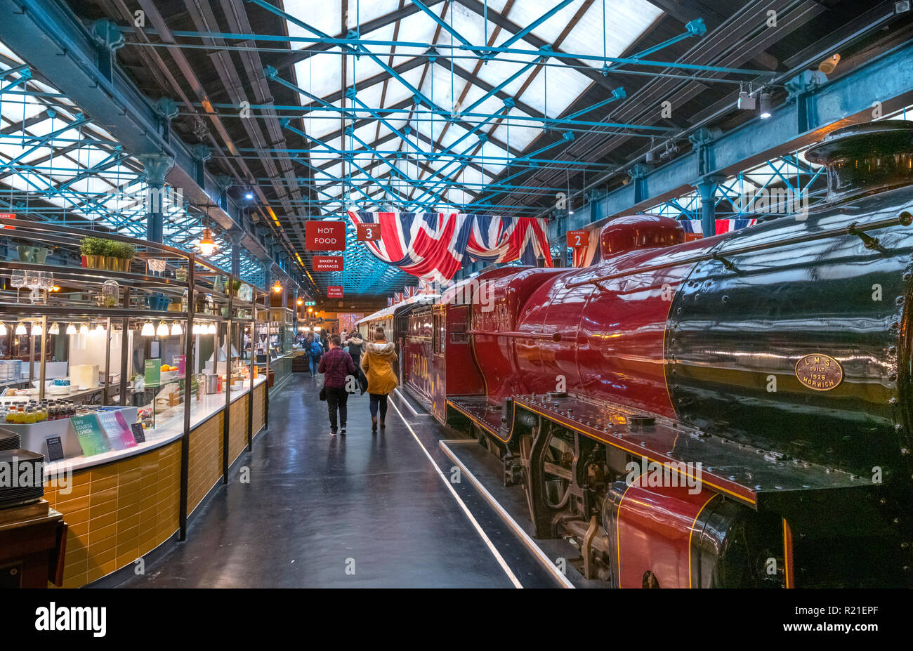 Steam train and cafes in the Station Hall, National Railway Museum, York, North Yorkshire, England UK - Stock Image