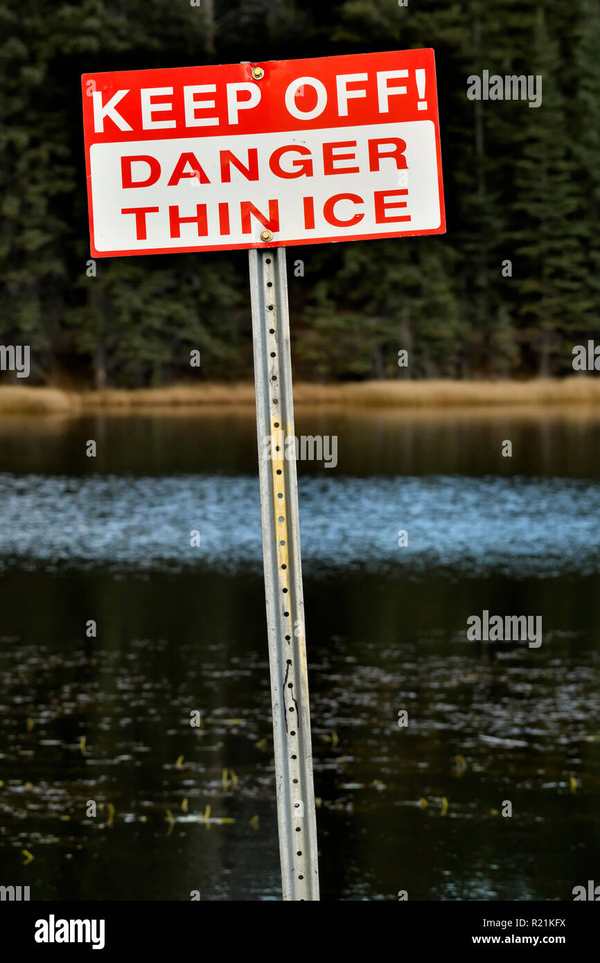 A vertical image of a  sign that warns of Thin Ice on an open water lake in rural Alberta Canada. - Stock Image