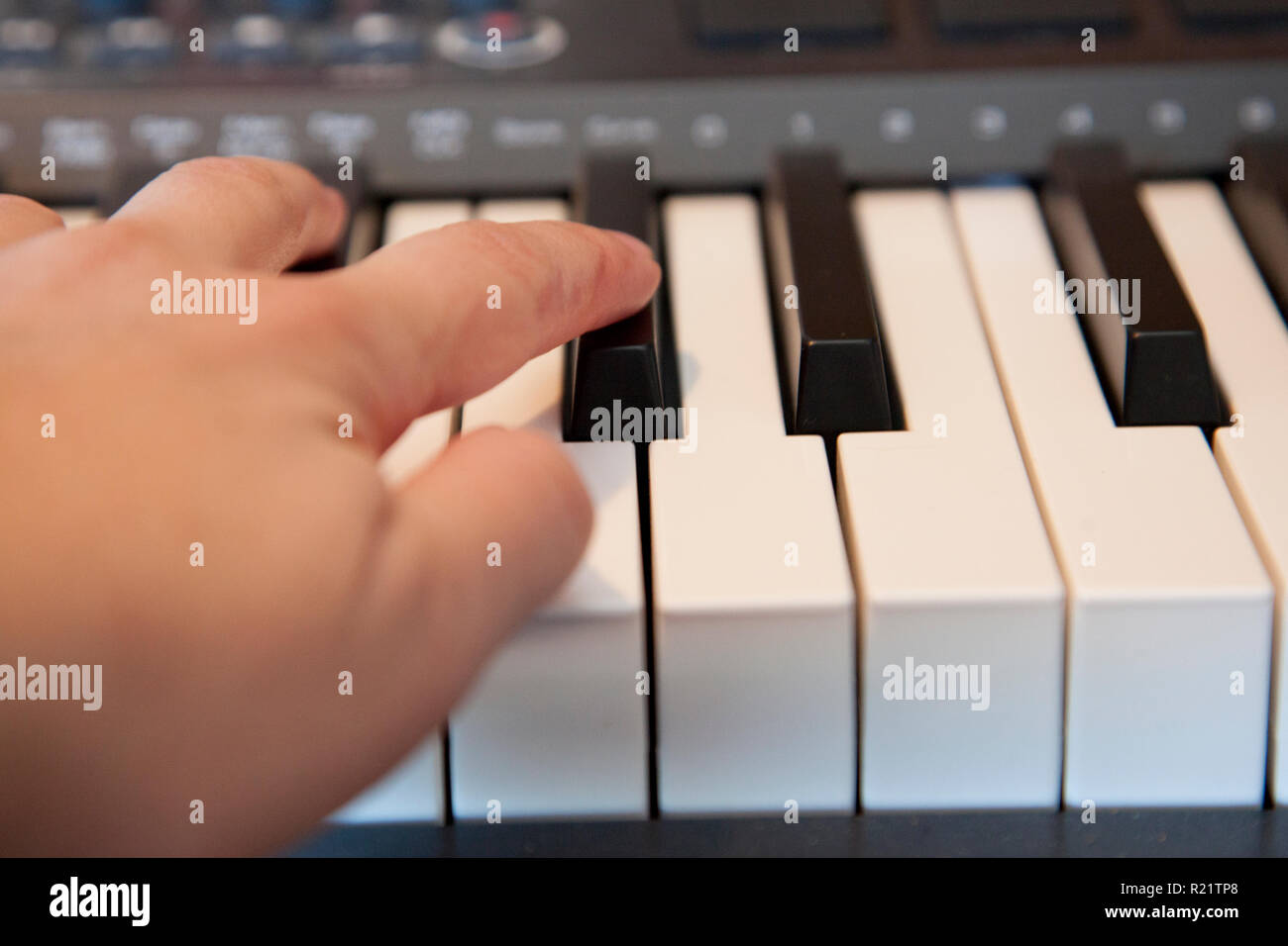 Fingers playing on a digital media keyboard or piano - Stock Image