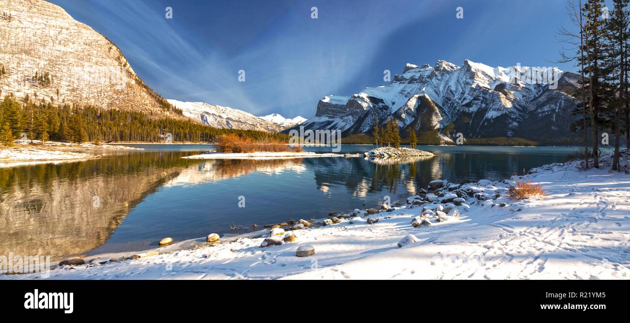 Wide Panoramic Scenic Landscape View Minnewanka Lake Shore and Distant Snowcapped Peaks after Autumn Snowfall in Banff National Park - Stock Image