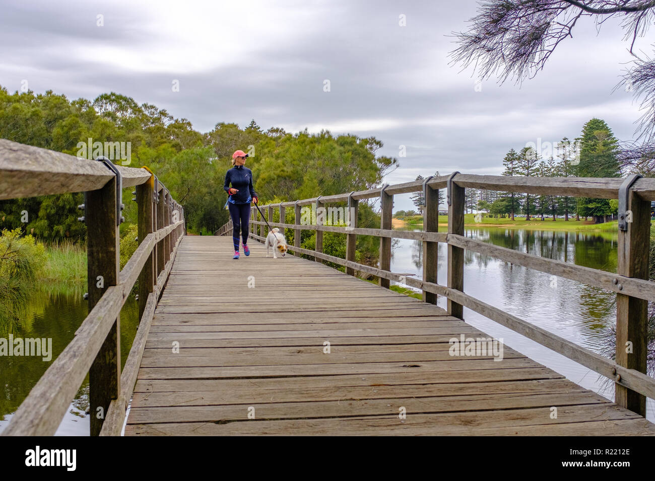 Woman  in sports lifestyle clothing outside enjoying unplugged me time walking towards with small dog on rustic wooden bridge across river. - Stock Image