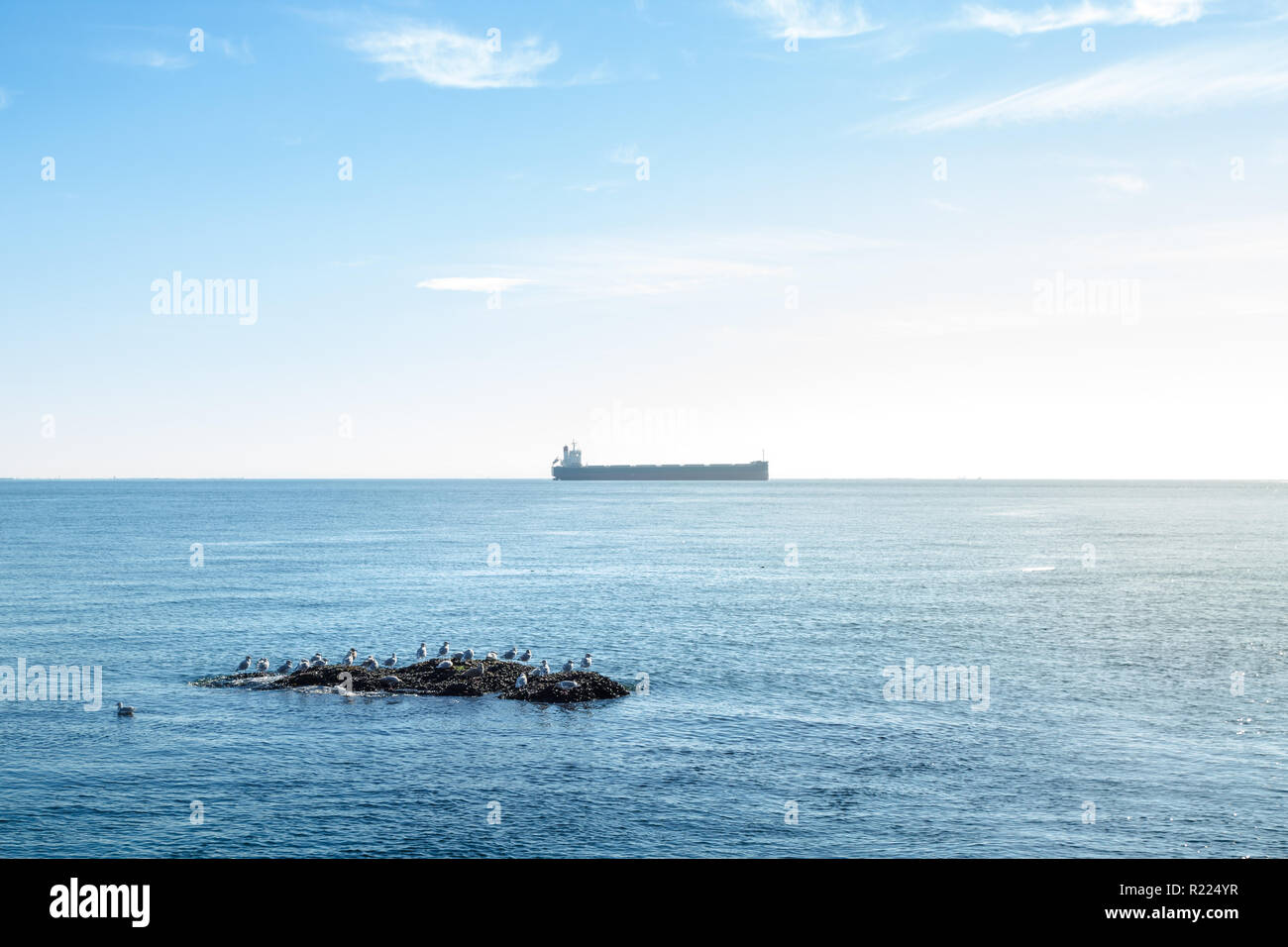 A view out onto the open ocean of the Georgia Strait of a gull rock and a tanker. - Stock Image