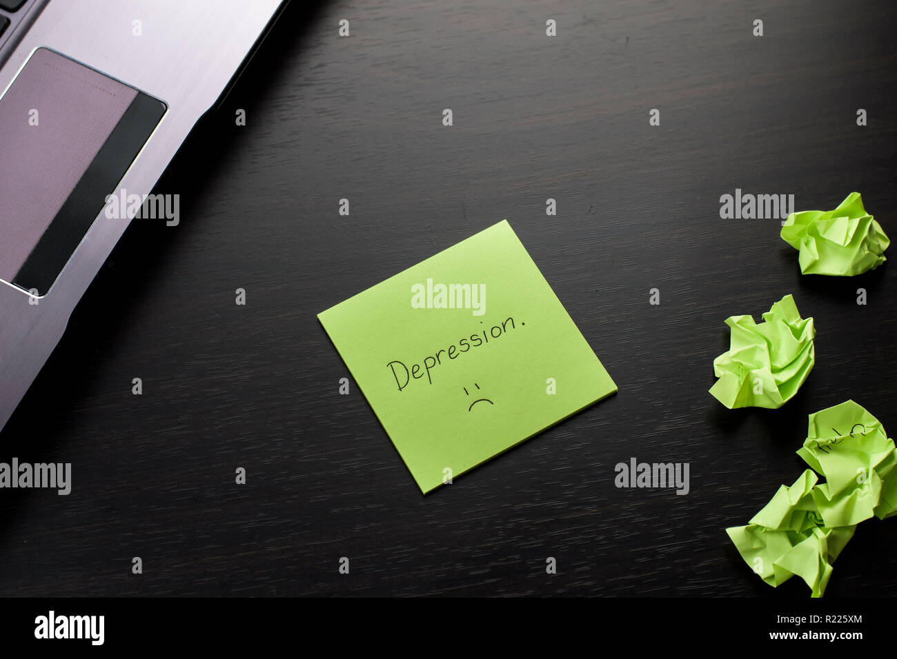 'Depression' is written on a green sticky note on wooden black table. Crumpled green sticky notes are scattered and a laptop computer on the side. - Stock Image
