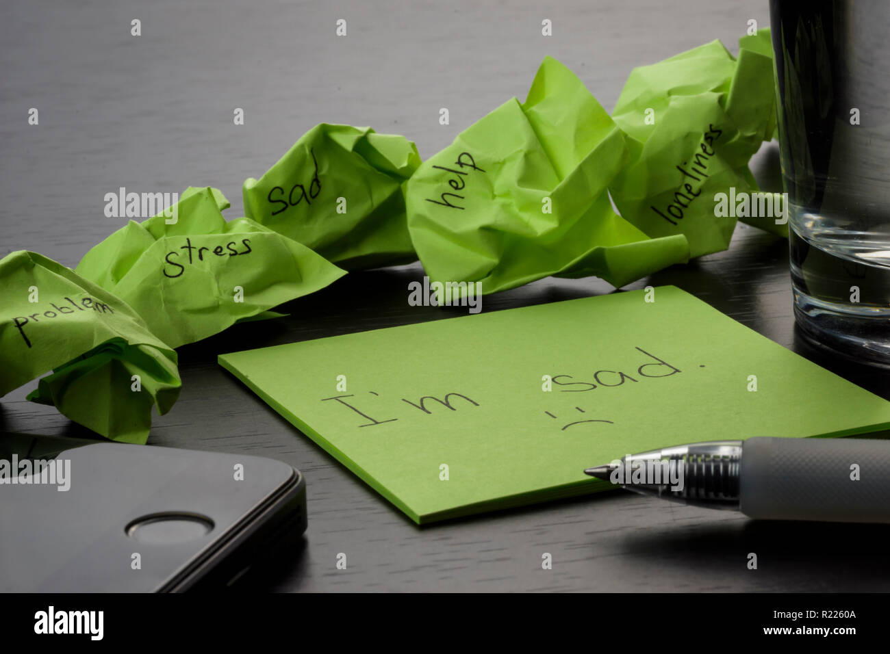 Depression. The phrase ''I'm sa' is written on a green sticky note on wooden black table. Crumpled green sticky notes are scattered with texts written. - Stock Image