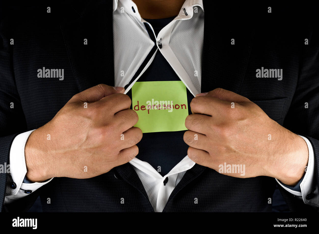 Hiding depression. A man in suit opening and unbuttoning his inner shirt to reveal his depression. Depression is written on a green sticky note. - Stock Image