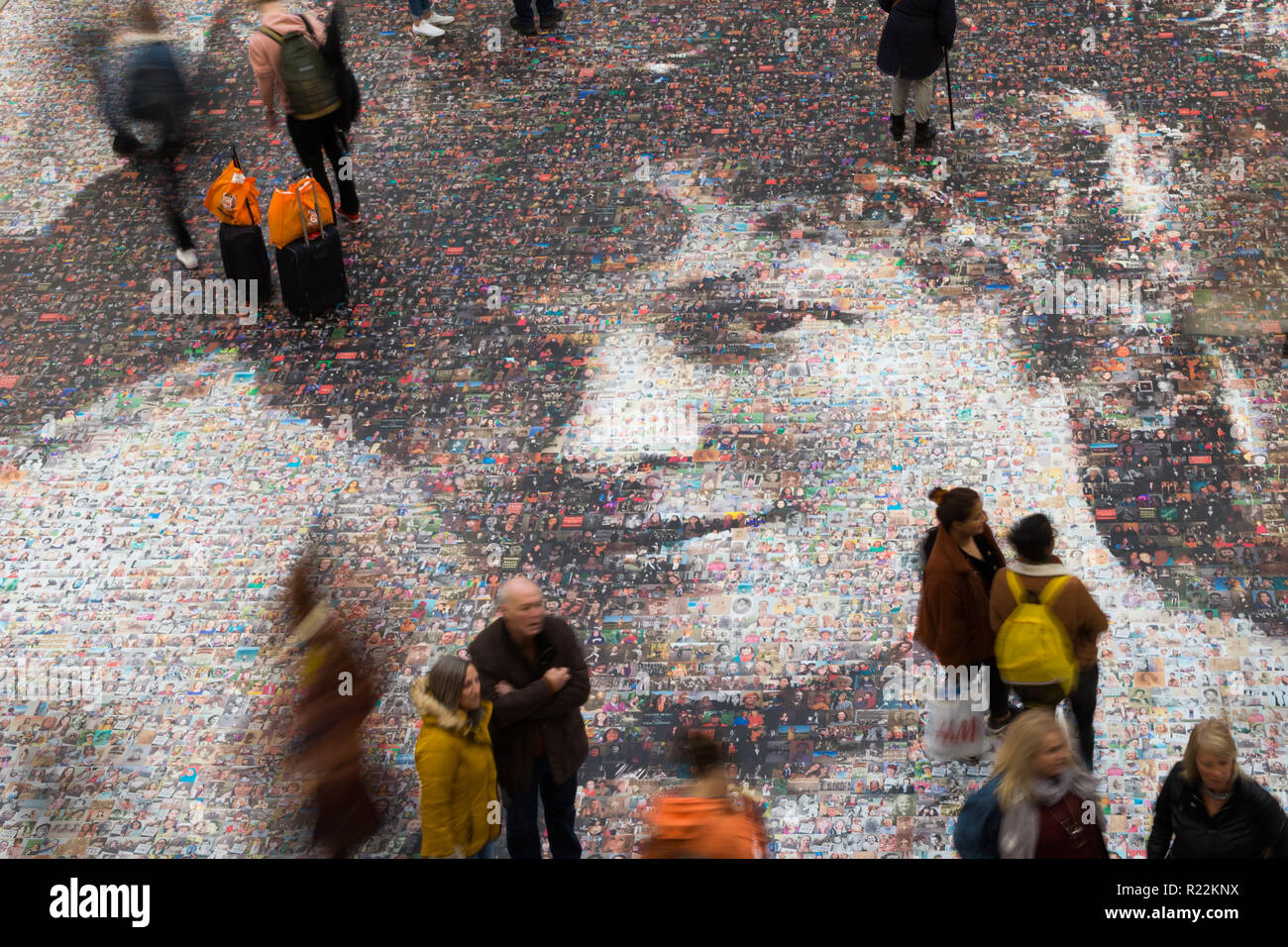 Birmingham, UK. 16th November, 2018. A large-scale mosaic portrait of sufragette Hilda Burkitt is on show on the concourse floor of New Street station, Birmingham. The 20 metre portrait is made up of 3,724 selfie photographs and other photographs of women sent in from all over the UK. The project, called Face of Suffrage, is deisgned by artist Helen Marshall. Hilda Burkitt was born in Wolverhampton in 1876, was convicted and jailed for breaking a window in the then Prime Minister's train carriage. Peter Lopeman/Alamy Live News - Stock Image