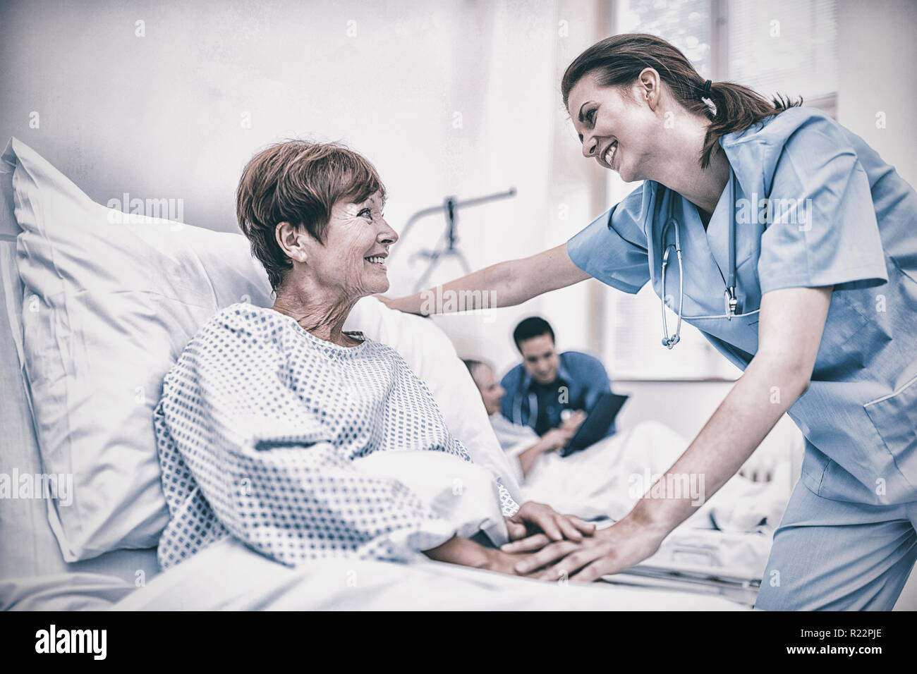 Nurse consoling a patient in hospital ward Stock Photo