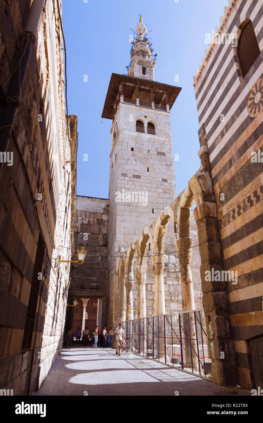 Damascus, Syria : Minaret of the Bride, the oldest of the Umayyad Mosque as seen from an alley in the old town. - Stock Image