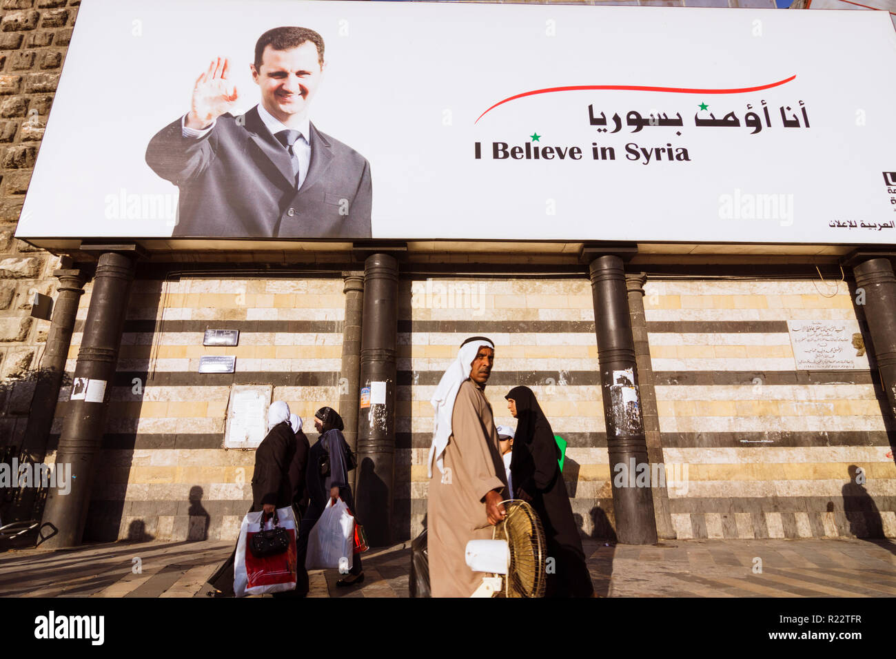 Damascus, Syria : People walk past a billboard of the president of Syria Bashar al-Assad reading I believe in Syria. - Stock Image