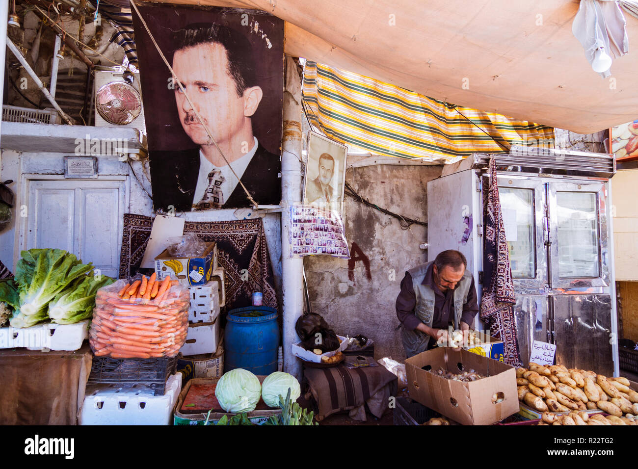 Damascus, Syria, May 29th 2009 : A vendor sells vegetables at a market stall dominated by a big portrait of the president of Syria, Bashar al-Assad. - Stock Image