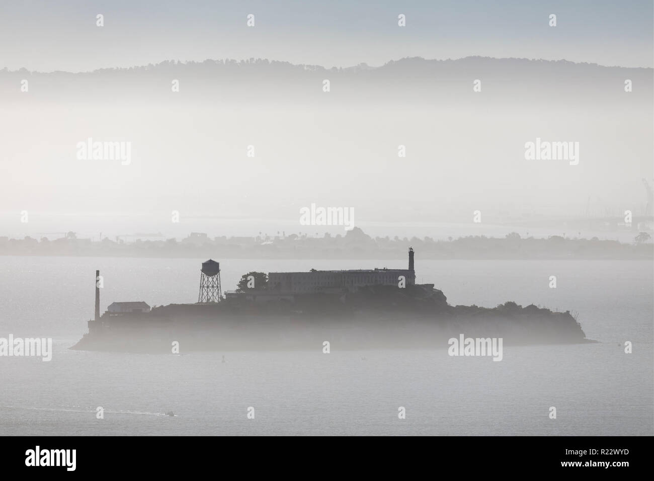 Alcatraz, in infamous prison of an island of the same name is viewed from afar in a foggy San Francisco Bay. - Stock Image