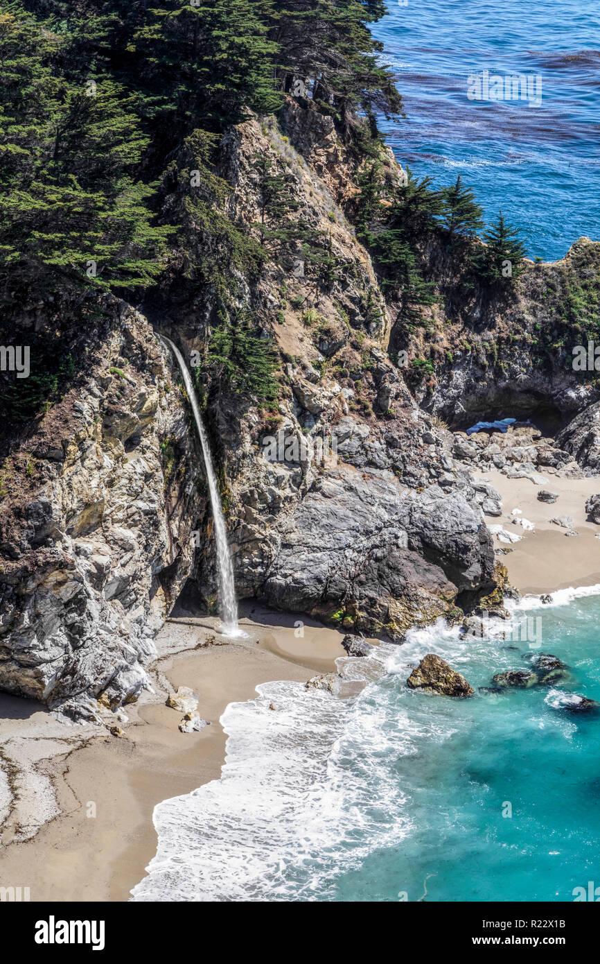 Plunging onto a beach from a rocky cliff along California's Big Sur coast, beautiful McWay Falls is said to be one of only two waterfalls in Californi - Stock Image