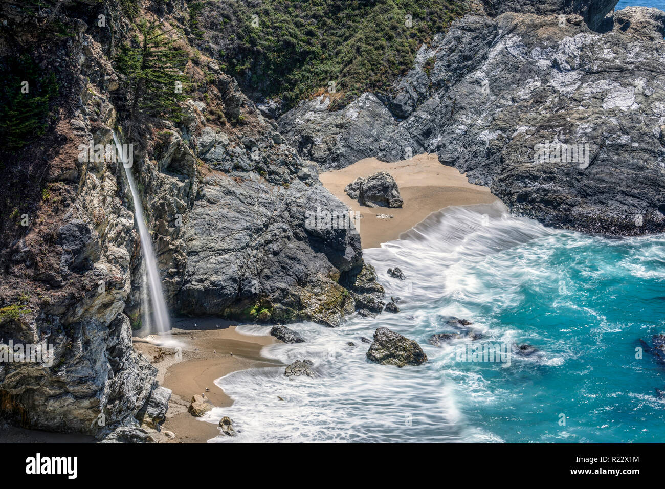 'McWay Falls Surf' Idyllic McWay Falls, along the Big Sur area of Central California, is said to be one of only two waterfalls in California that empt - Stock Image
