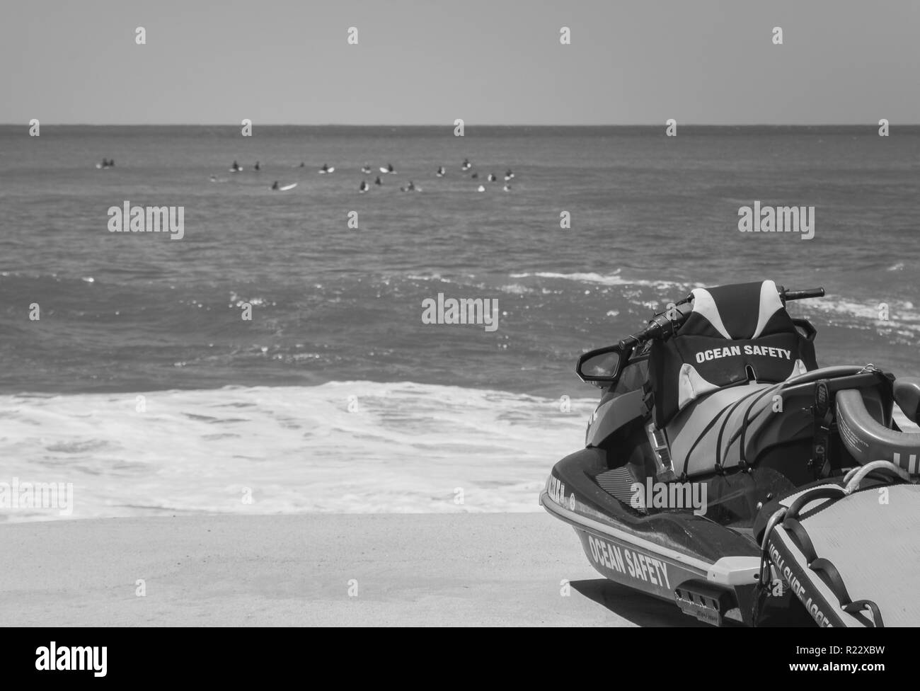 Black and white of a group of surfers off in the distance in the water as a lifeguard jetski sits on the beach that reads ocean safety ready to be cal - Stock Image