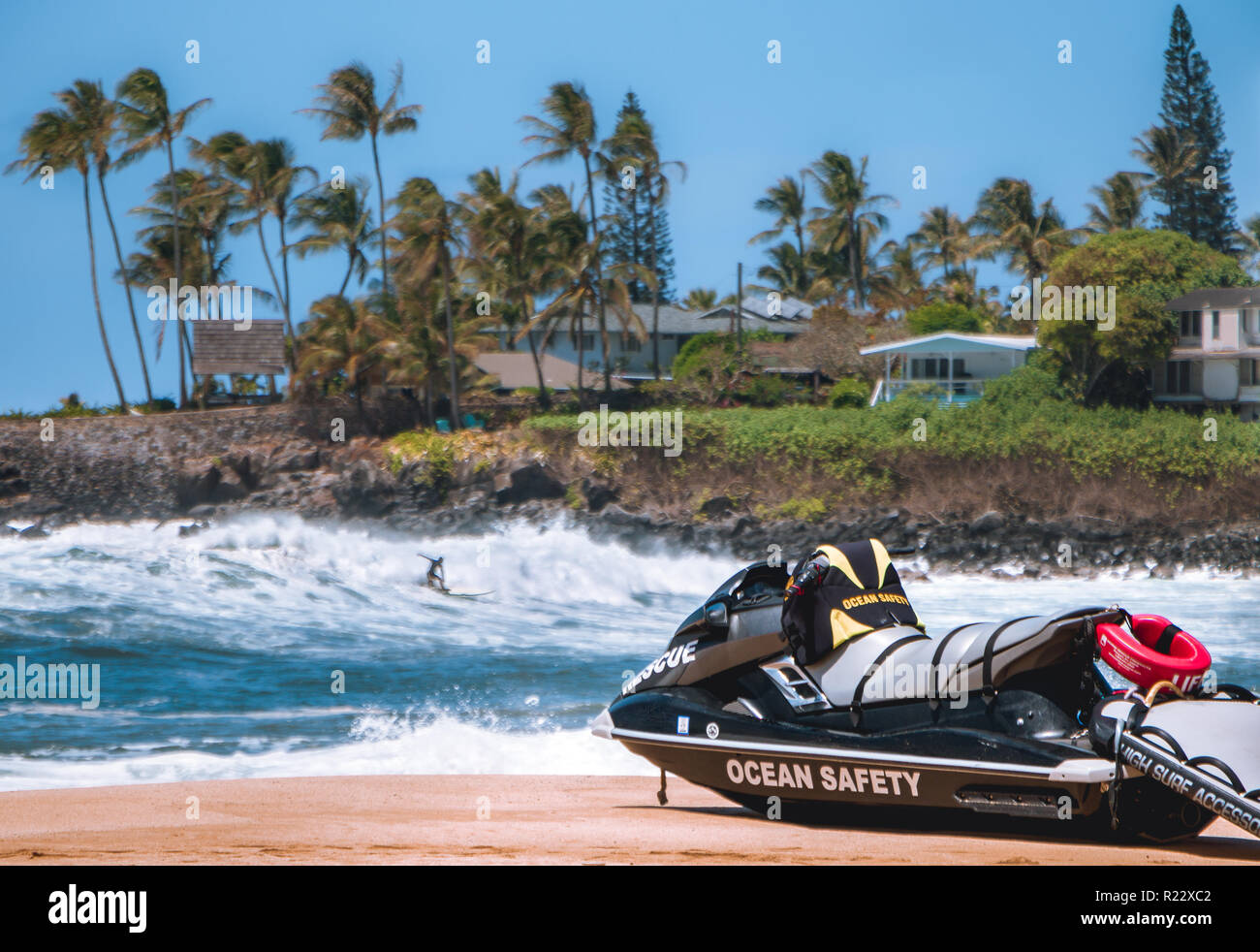A single sufers hits a wave in fround of rocks and houses in the blured background as a lifeguard rescue jetski sets on the beach the reads ocean safe - Stock Image