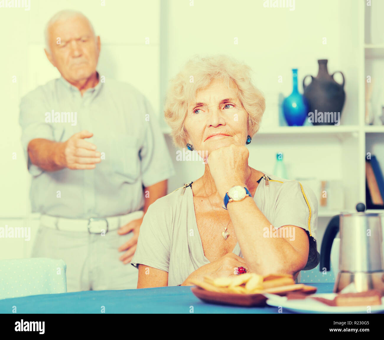 Upset mature woman dont speaking after discord with man standing behind - Stock Image