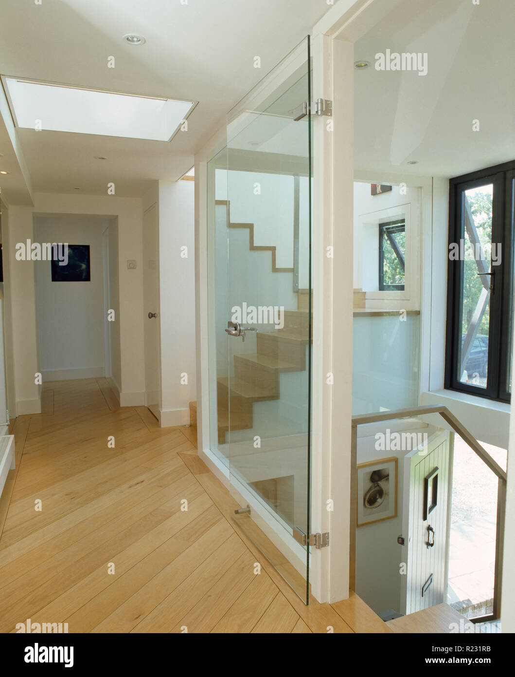Modern landing with glass wall and wooden flooring - Stock Image