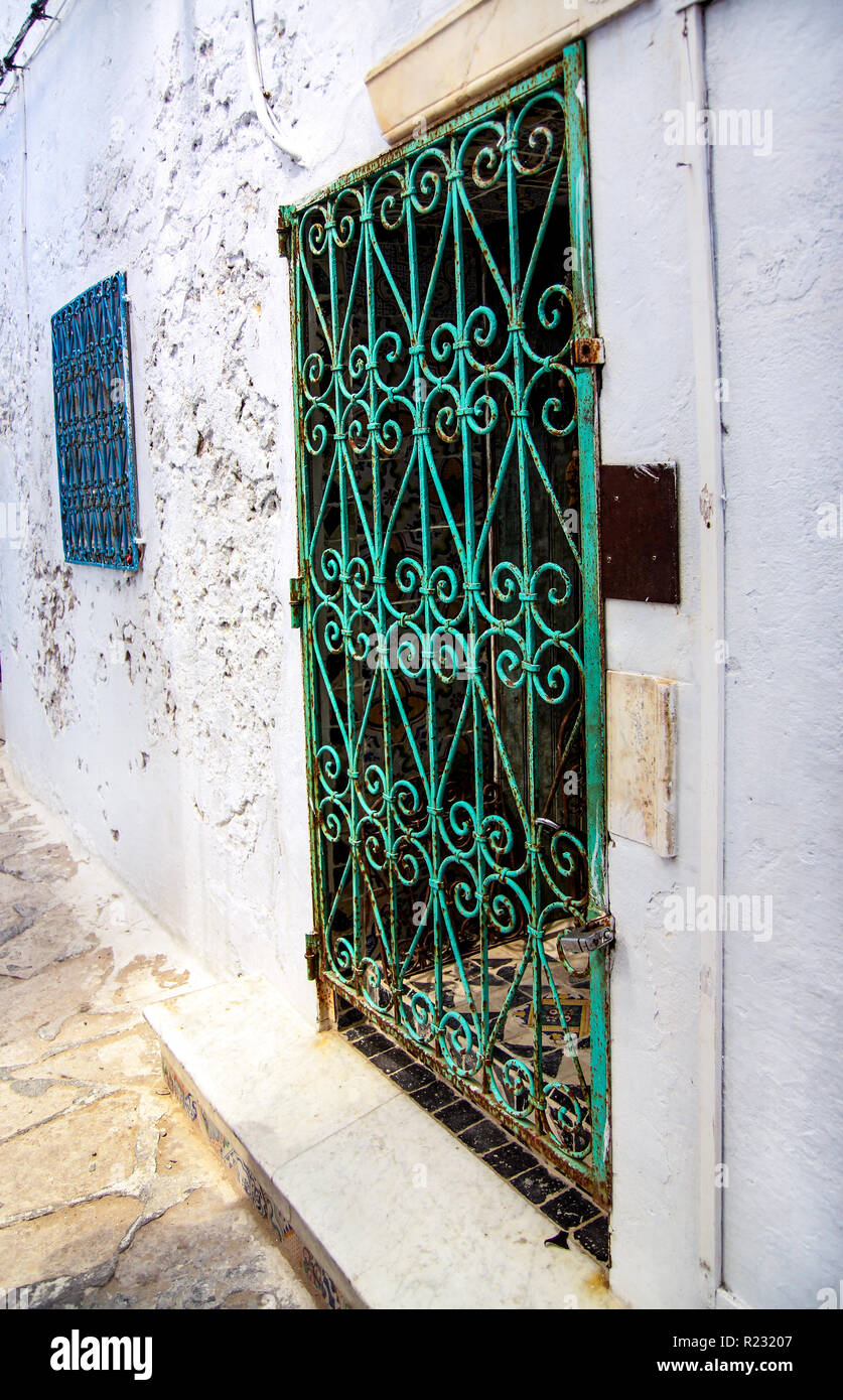 Beautiful ornamental windows on white wall typical for Tunisia / Traditional old green window with ornament decorative forging in historical district. Stock Photo