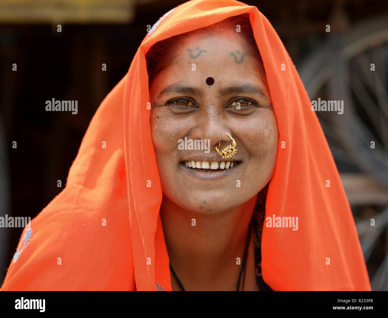 Middle-aged Rajasthani woman with traditional nose jewelry and tribal tattoos on chin and forehead wears an orange headscarf (dupatta). Stock Photo